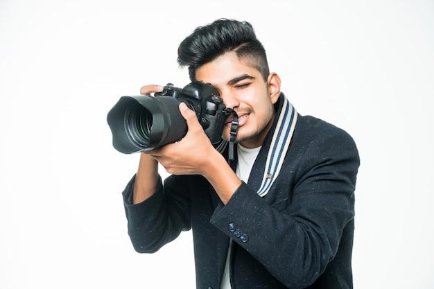 Indischer fotograf mann, der seine kamera auf einem weißen hintergrund hält.