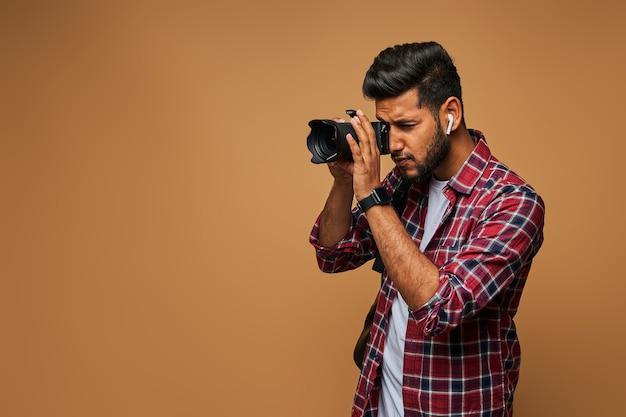 Indischer fotograf mit kamera an pastellfarbener wand