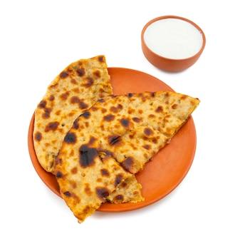 Indischer frühstücksteller aloo paratha diente mit klumpen auf weißem hintergrund