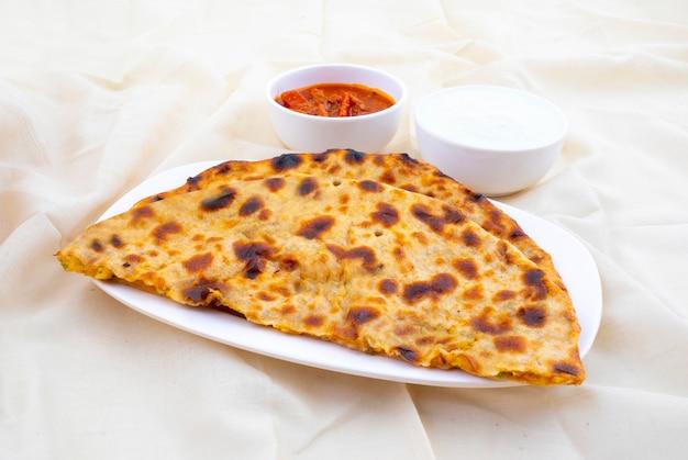 Indischer frühstücksteller aloo paratha diente mit klumpen und essiggurke