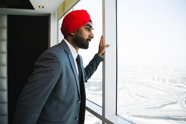 Indischer geschäftsmann, der aus dem fenster in seinem büro schaut