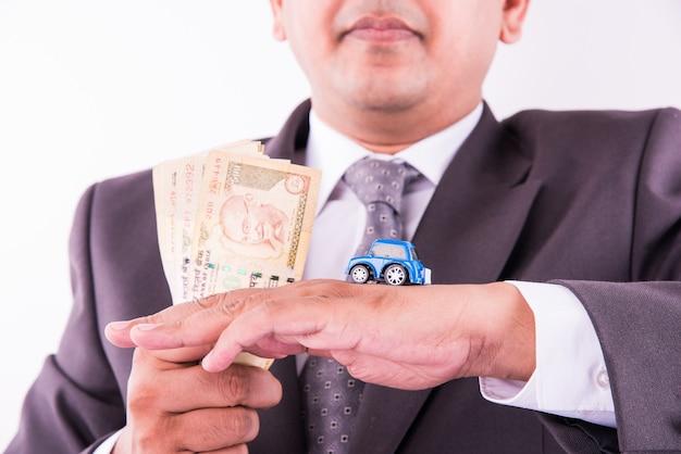 Indischer geschäftsmann, der geldscheine und spielzeugauto mit schlüssel hält, autokonzept kauft