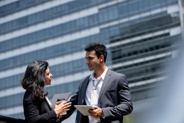 Indischer geschäftsmann, der sitzung im freien mit kunden hat