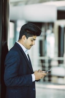 Indischer geschäftsmann, der smartphone im büro liest oder benutzt