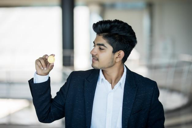 Indischer geschäftsmann im anzug mit goldenem bitcoin im modernen büro