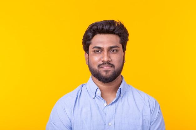 Indischer hübscher mann, der blaues hemd auf gelber wand trägt