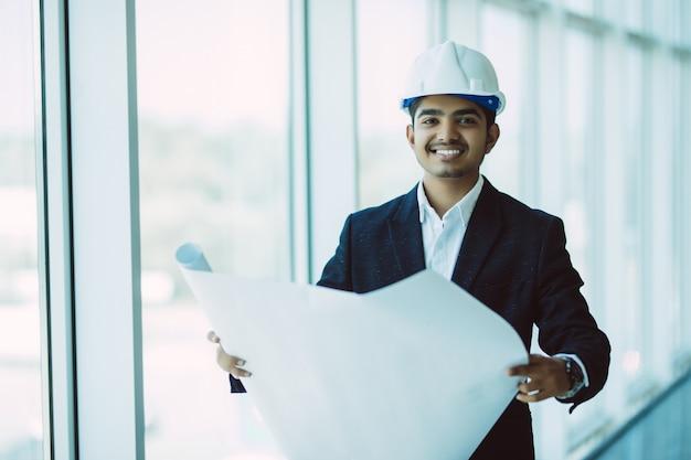 Indischer ingenieur bei der arbeit auf einer baustelle