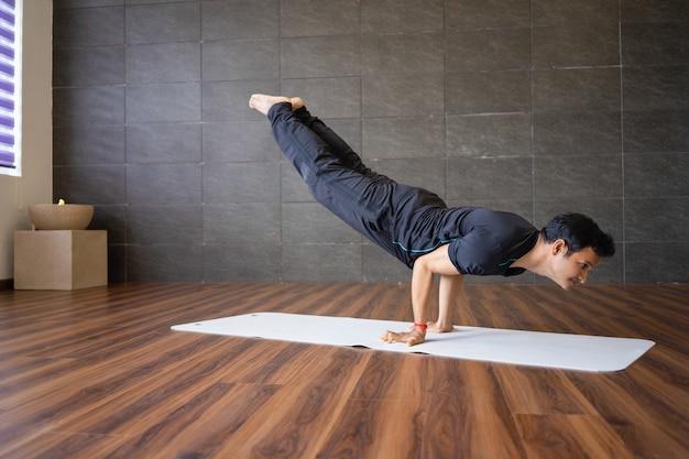 Indischer jogi, der fortgeschrittene handstandyogahaltung in der turnhalle tut