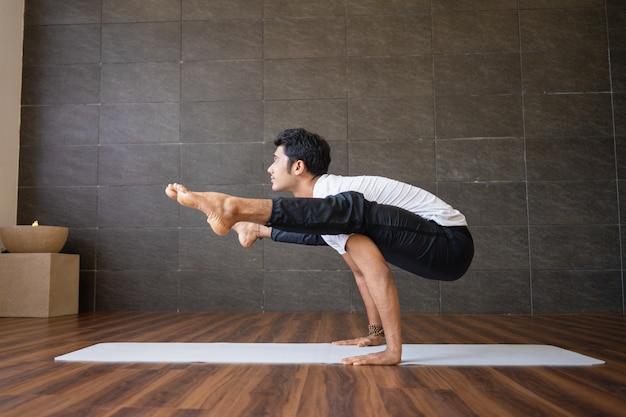 Indischer jogi, der leuchtkäferyogahaltung in der turnhalle tut