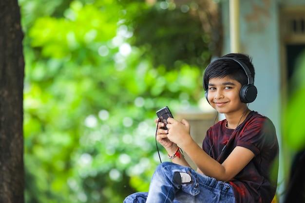 Indischer junge, der musik hört oder auf handy lernt