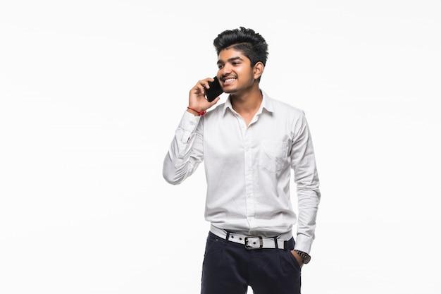 Indischer junger geschäftsmann, der im handy auf weißer wand spricht.