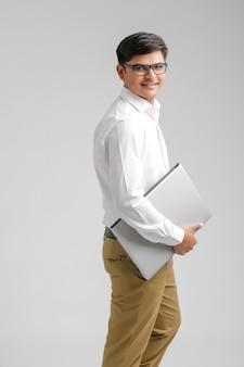 Indischer junger mann, der einen laptop anhält