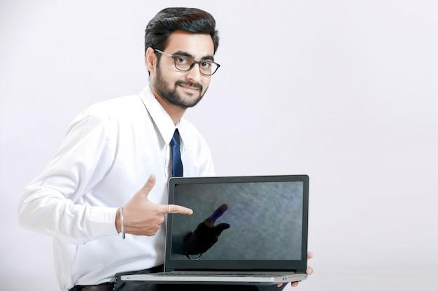 Indischer junger mann, der laptopschirm zeigt