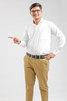 Indischer junger mann, der richtung mit der hand zeigt