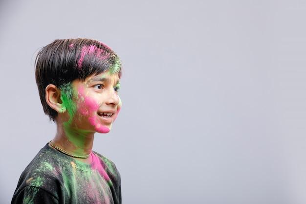 Indischer kleiner junge, der mit der farbe in holi festival spielt