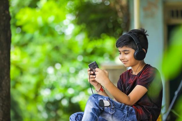 Indischer kleiner junge, der musik auf smartphone hört