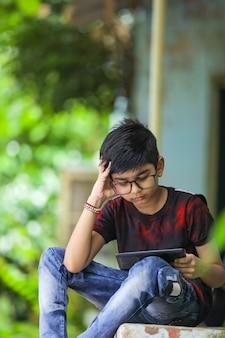 Indischer kleiner junge, der online mit handy zu hause studiert