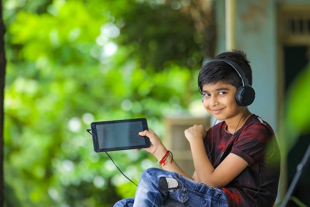 Indischer kleiner junge, der smartphonebildschirm zeigt