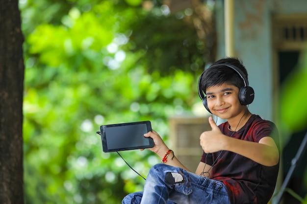 Indischer kleiner junge, der tablettbildschirm zeigt