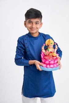 Indischer kleiner junge in ethnischer kleidung und laxmi-skulptur in der hand haltend