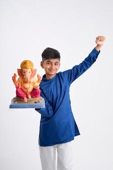 Indischer kleiner junge mit lord ganesha, der ganesh festival feiert