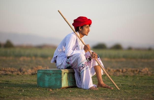 Indischer ländlicher junge, der auf weinlesekiste sitzt