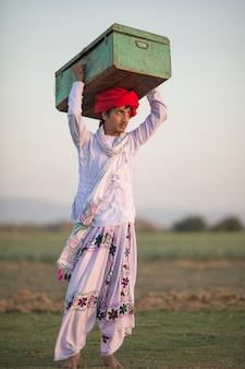 Indischer ländlicher junge, der sutcase auf kopf hält