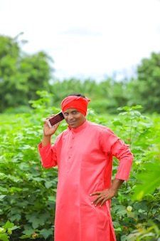 Indischer landwirt, der auf handy am landwirtschaftsfeld spricht
