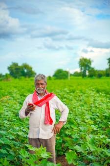 Indischer landwirt, der handy am landwirtschaftsfeld verwendet