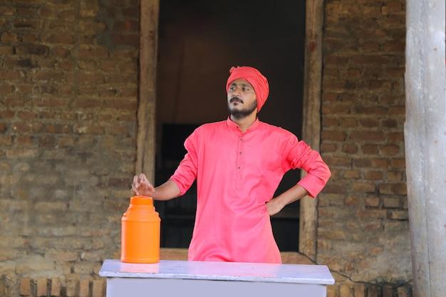 Indischer landwirt, der milchflasche in der hand auf milchfarm hält