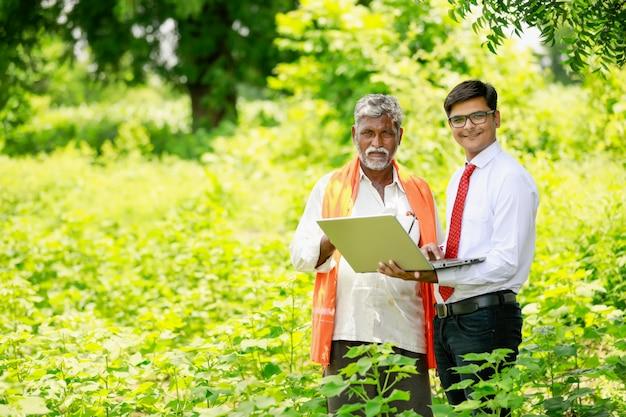 Indischer landwirt mit agronom am baumwollfeld