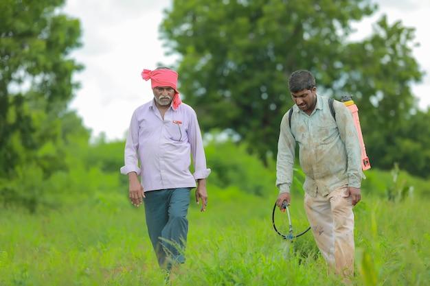 Indischer landwirt und arbeit, die pestizid auf feld sprühen