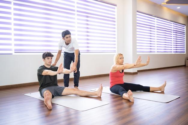 Indischer lehrer hilft studenten an der yogaklasse