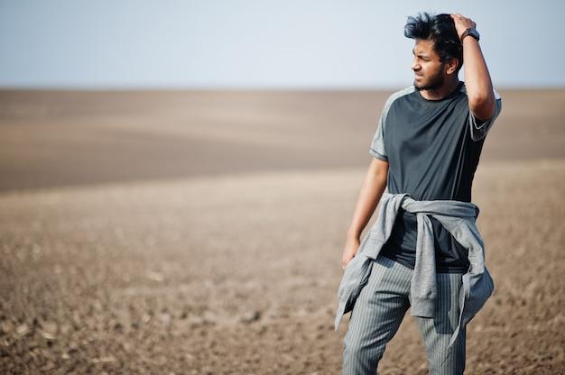 Indischer mann an der freizeitkleidung warf am feld allein auf.