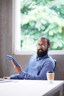 Indischer mann, der am schreibtisch im büro mit tablette sitzt und in richtung zur kamera schaut
