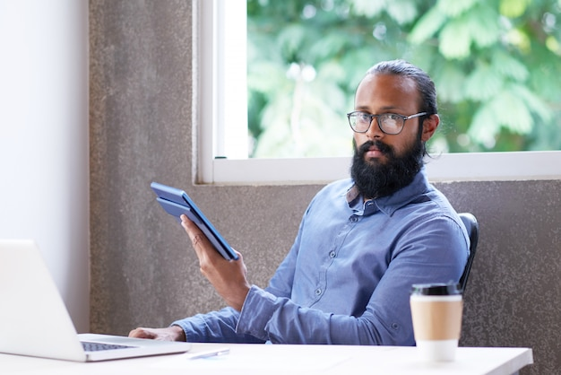 Indischer mann, der am schreibtisch im büro sitzt und tablette verwendet