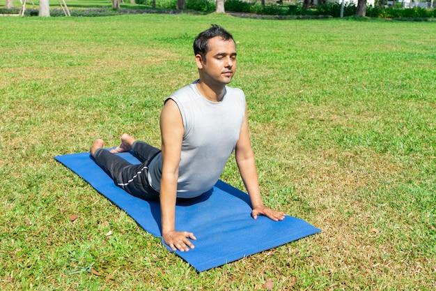Indischer mann, der aufwärts aufpassende hundehaltung draußen auf grünem rasen tut. outdoor-yoga-konzept