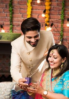 Indischer mann, der frau, schmuck zum diwali- oder hochzeitstag ein überraschungsgeschenk gibt, selektiver fokus