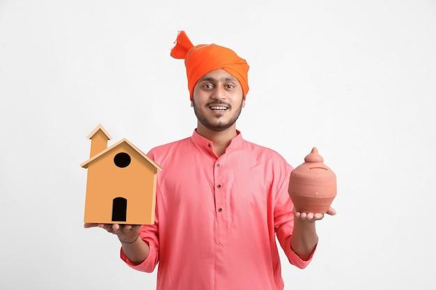 Indischer mann, der handgemachtes haus und tonschweinchenbank in der hand hält