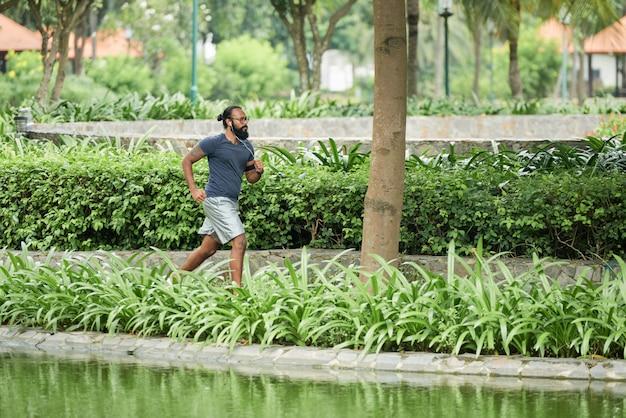 Indischer mann, der im park rüttelt