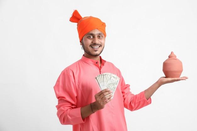 Indischer mann, der sparschwein und währung des lehms in der hand auf weißer wand hält
