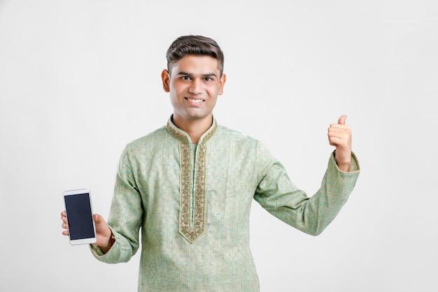 Indischer mann in der ethnischen abnutzung und im zeigen des smartphone