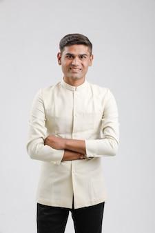 Indischer mann in der ethnischen abnutzung und in der stellung über weiß