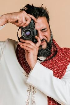 Indischer mann in einer kurta mit einer digitalkamera