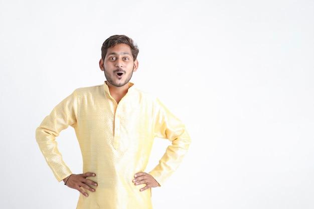 Indischer mann in traditioneller kleidung und aufgeregtem ausdruck auf weißer wand