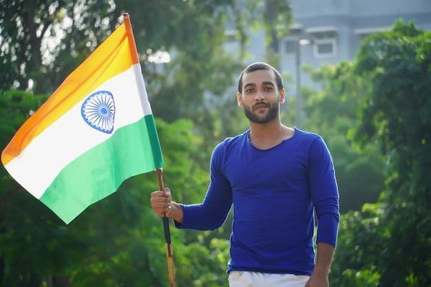 Indischer mann mit indischer flagge im freien
