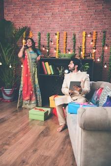 Indischer mann mit tab- oder tablet-touchscreen-computer und frau, die diyas im hintergrund am diwali-festivaltag beleuchtet?