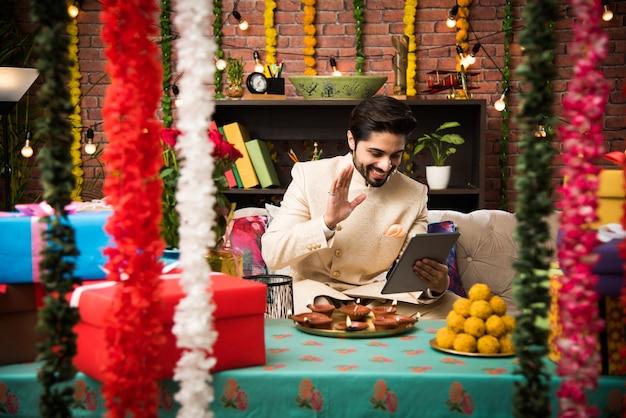 Indischer mann mit tablet-touchscreen-computer am festivaltag, während er traditionelles outfit trägt. auf dem sofa sitzen mit geschenken und süßigkeiten mit beleuchtung bokeh