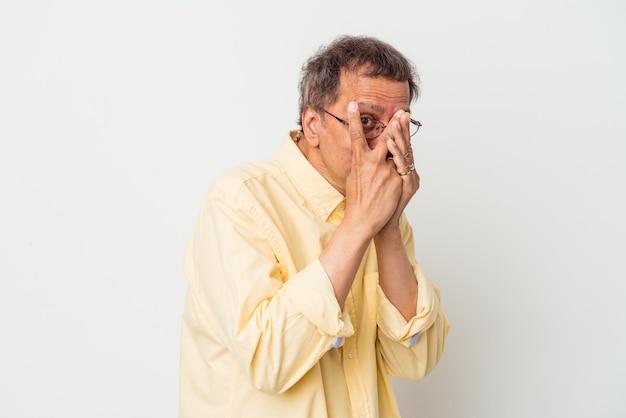 Indischer mann mittleren alters isoliert auf weißem hintergrund blinzelt erschrocken und nervös durch die finger.