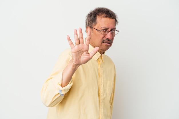 Indischer mann mittleren alters isoliert auf weißem hintergrund, der jemanden ablehnt, der eine geste des ekels zeigt.